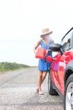 Comprimento completo do carro do reabastecimento da jovem mulher na estrada secundária Fotografia de Stock Royalty Free