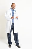 Comprimento completo do doutor indiano maduro usando o tablet pc Fotografia de Stock
