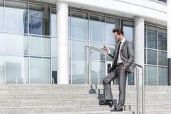 Comprimento completo do envio de mensagem de texto do homem de negócios através do telefone celular ao estar em etapas fora do es Foto de Stock