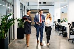 Comprimento completo do grupo de executivos novos felizes que andam o corredor no escritório junto imagens de stock royalty free