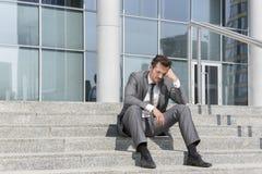 Comprimento completo do homem de negócios forçado que senta-se em etapas fora do escritório Imagens de Stock Royalty Free