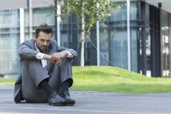 Comprimento completo do homem de negócios triste que senta-se no trajeto fora do escritório fotografia de stock