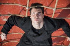 Comprimento completo do homem 20s sério na corda climbling Fotografia de Stock Royalty Free