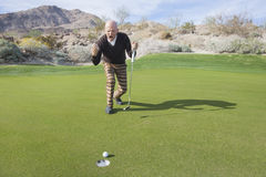 Comprimento completo do jogador de golfe masculino superior que comemora a tacada leve de naufrágio no campo de golfe Fotos de Stock Royalty Free