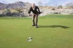 Comprimento completo do jogador de golfe masculino superior que comemora uma tacada leve no campo de golfe foto de stock royalty free