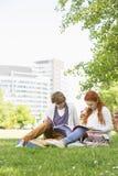 Comprimento completo dos amigos masculinos e fêmeas novos que estudam no terreno da faculdade foto de stock royalty free
