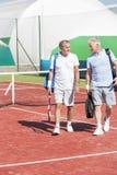 Comprimento completo dos homens na roupa dos esportes que falam ao andar no campo de tênis durante o fim de semana do verão imagens de stock royalty free