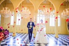 Comprimento completo dos pares elegantes do casamento que guardam as mãos na igreja Fotos de Stock