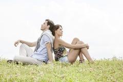 Comprimento completo dos pares novos pensativos que sentam-se de volta à parte traseira no parque Imagem de Stock Royalty Free