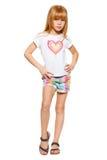 Comprimento completo uma menina com cabelo vermelho no short e em um t-shirt; isolado no fundo branco foto de stock royalty free
