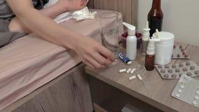 Comprimido da tomada da mulher e posto no vidro da água filme