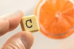 Comprimido da vitamina c entre os dedos e a laranja fresca Imagem de Stock Royalty Free