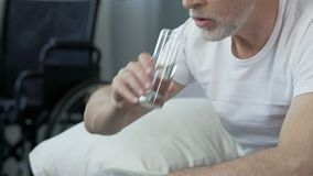 Comprimido e água potável de tomada masculinos infelizes, tratamento no centro de reabilitação filme