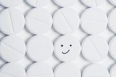 Comprimido feliz cercado pelos comprimidos brancos da prescrição Imagem de Stock Royalty Free