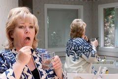 Comprimido maduro da mulher na lingüeta Fotografia de Stock