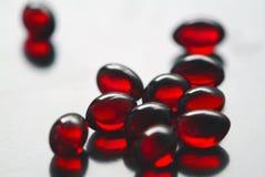 Comprimidos alaranjados macios na em um vidro Fotografia de Stock