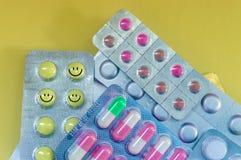 Comprimidos amarelos com um sorriso, cápsulas brancas vermelhas, tabuletas redondas cor-de-rosa em um fundo amarelo fotos de stock royalty free