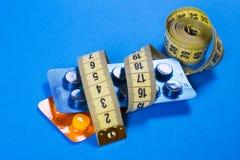 Comprimidos amarelos da fita do centímetro nas tiras Fundo da medicina de Imagens de Stock Royalty Free