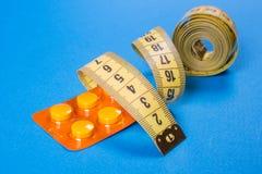 Comprimidos amarelos da fita do centímetro nas tiras Fundo da medicina de Fotografia de Stock