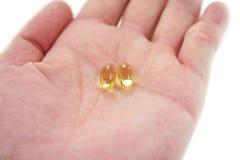 Comprimidos amarelos do gel da preensão dois da mão fotos de stock royalty free