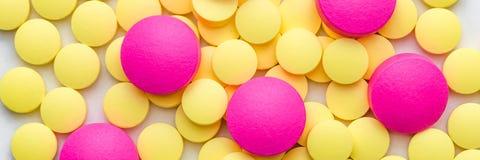 Comprimidos amarelos e cor-de-rosa em um fundo branco fotografia de stock royalty free