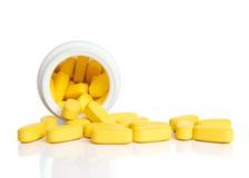 Comprimidos amarelos e uma garrafa Fotografia de Stock Royalty Free