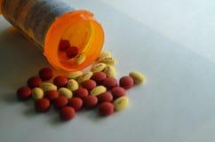 Comprimidos amarelos e vermelhos da prescrição em uma garrafa de comprimido Fotos de Stock