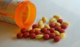 Comprimidos amarelos e vermelhos da prescrição por uma garrafa de comprimido Imagens de Stock