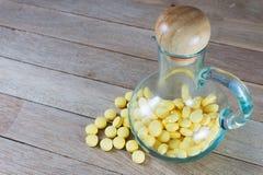 Comprimidos amarelos na garrafa de vidro com o bico no fundo de madeira foto de stock