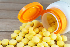 Comprimidos amarelos na garrafa plástica no fundo de madeira foto de stock