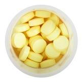 Comprimidos amarelos no fim plástico redondo da garrafa acima Imagem de Stock