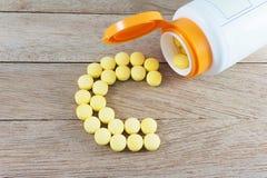 Comprimidos amarelos que formam a forma ao alfabeto de C no fundo de madeira imagens de stock
