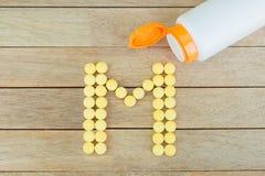 Comprimidos amarelos que formam a forma ao alfabeto de M no fundo de madeira Fotografia de Stock