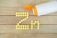 Comprimidos amarelos que formam a forma ao alfabeto do Zn no fundo de madeira Fotos de Stock Royalty Free