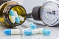 Comprimidos azuis e brancos, recipiente transparente Imagens de Stock