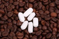 Comprimidos brancos com feijões de café Fotos de Stock