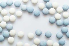 Comprimidos brancos e azuis na superfície da luz Fotos de Stock Royalty Free