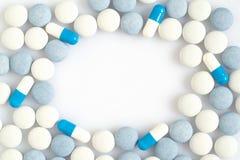 Comprimidos brancos e azuis na superfície da luz Imagens de Stock Royalty Free