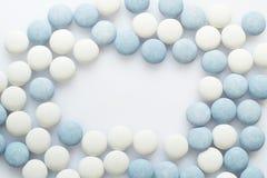 Comprimidos brancos e azuis na superfície da luz Imagem de Stock Royalty Free