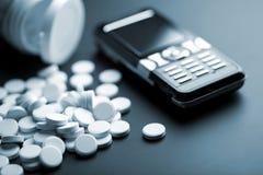 Comprimidos brancos e telefone móvel Fotografia de Stock Royalty Free