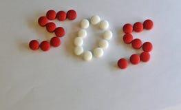 Comprimidos brancos e vermelhos da prescrição em S O S Fotografia de Stock Royalty Free