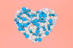 Comprimidos coloridos apresentados na forma do coração Imagens de Stock Royalty Free