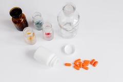Comprimidos coloridos nas garrafas de vidro no fundo branco fotografia de stock
