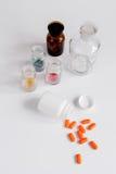 Comprimidos coloridos nas garrafas de vidro no fundo branco imagens de stock