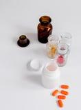 Comprimidos coloridos nas garrafas de vidro no fundo branco fotos de stock royalty free