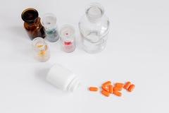 Comprimidos coloridos nas garrafas de vidro no fundo branco fotos de stock