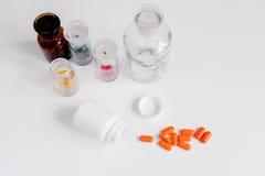Comprimidos coloridos nas garrafas de vidro no fundo branco imagem de stock