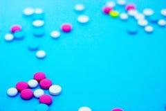 Comprimidos coloridos no fundo azul com espa?o da c?pia imagens de stock royalty free