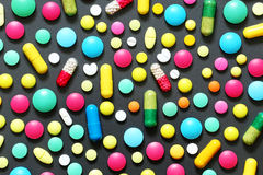 Comprimidos coloridos no fundo cinzento escuro Fotografia de Stock