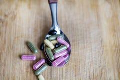 Comprimidos cor-de-rosa, brancos e pretos em uma colher do metal em um fundo de madeira Foto de Stock